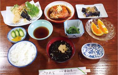 【神津島】 平和荘 明日葉の天ぷらや胡麻和え、金目鯛の煮付けなど、新鮮な島の食材を中心とした夕食です。 写真は一例で季節や仕入れ状況により内容が異なりますが、いろいろな料理で平和荘の家庭的な味をお楽しみください。