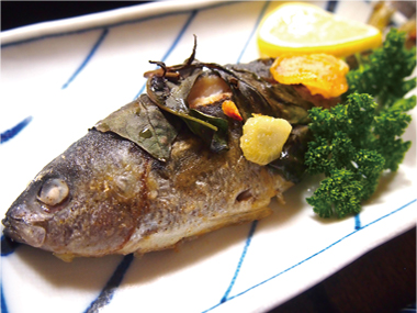 【式根島】湯たり宿 ひだぶんGH タカベは夏の伊豆諸島を代表する魚の一つで、身は柔らかく脂ののった白身魚です。 オリーブオイル、ニンニク、バジルでこんがり焼きあげた一品です。