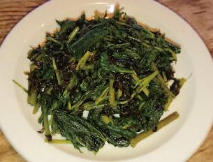 【伊豆大島】居酒屋 南島館 山菜と海藻がマッチした、明日葉とらっぱのり炒めです。店主のこだわりで「生の」らっぱのりを使用しており、他のお店ではなかなか出会えない素材の活かし方です。