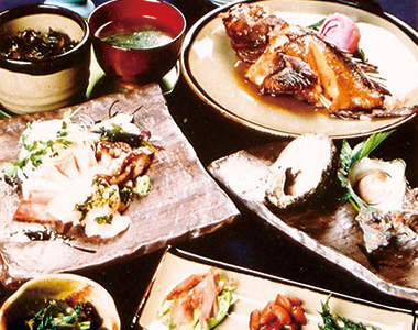 【伊豆大島】バリアフリーペンション「すばる」 その日に水揚げされた魚を中心にメニューを考え、お品書きを添えて、料理を提供しています。 (例)明日葉のナムル、お造り、真鯛の兜塩焼き、 カツオのまご茶漬け等